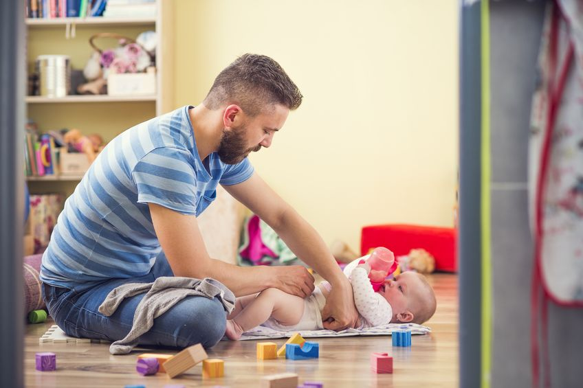 40317124 - young hipster father changing nappy to his little baby daughter