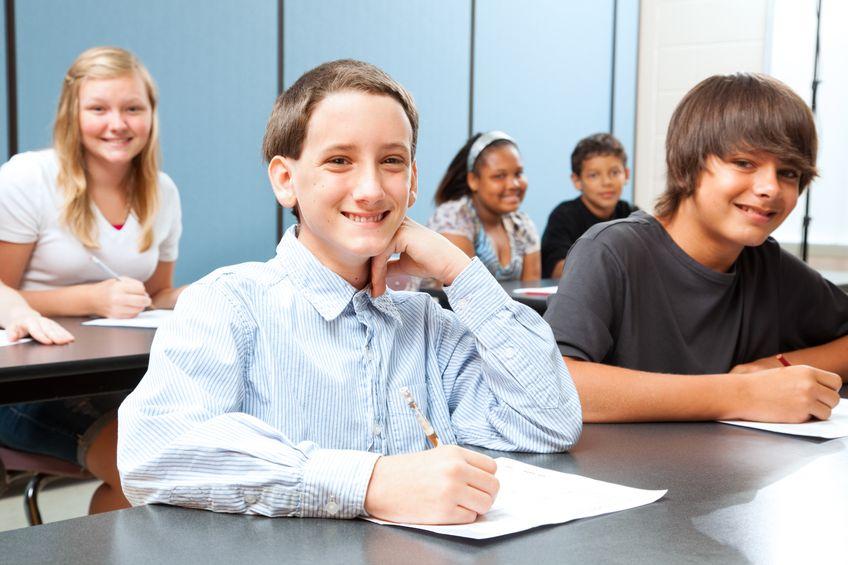 18351314 - cute boy in middle school class taking a test