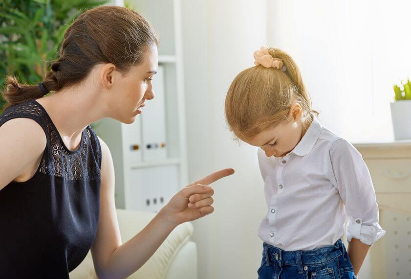 片付けない子供を叱る母