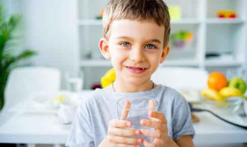 水分を摂って便秘予防をする子供