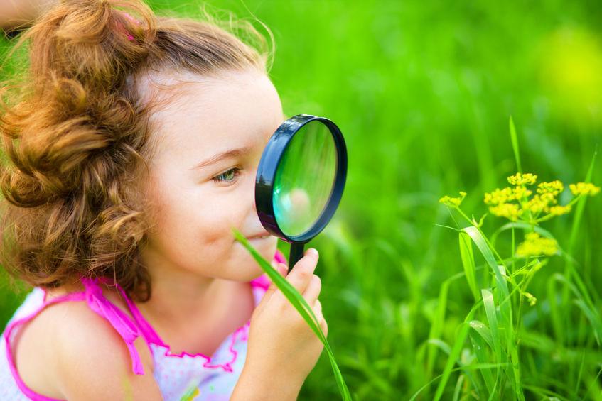 虫眼鏡で花を観察する子供