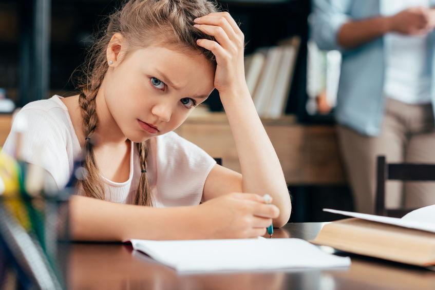 怒りながら勉強をする子供