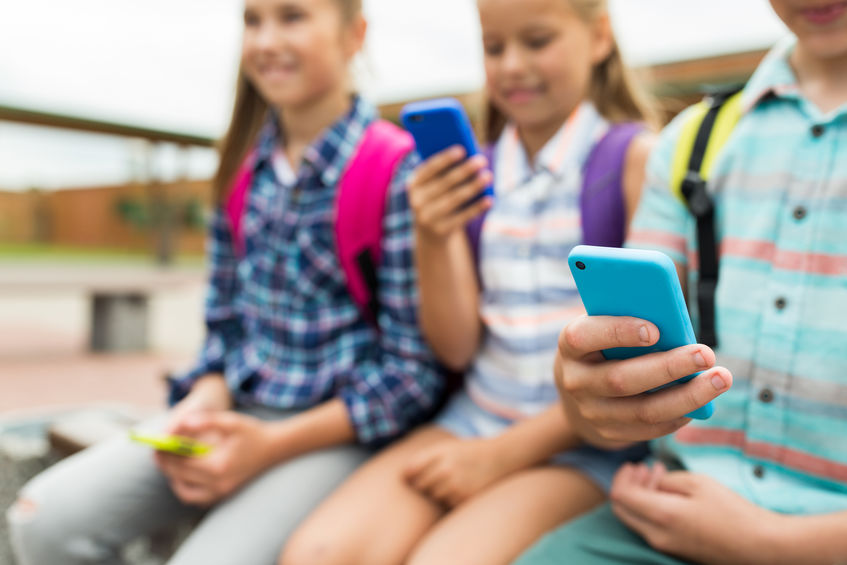 携帯電話を持つ小学生