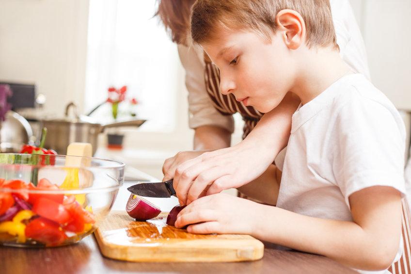 キッチンで料理をする小学生